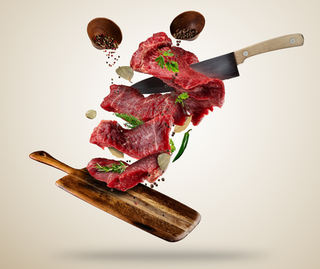 Flying pieces of raw steaks, with ingredients for cooking, served on woodenboard. Knife cuting the meat. Concept of food preparation in low gravity mode. Separated on smooth background Banque d'images