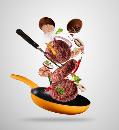 Flying raw milled hamburger meats pieces, with ingredients for cooking. Freeze motion of cooking staff and pan. Fork holding the meat. Concept of food preparation in low gravity mode. Separated on gray background