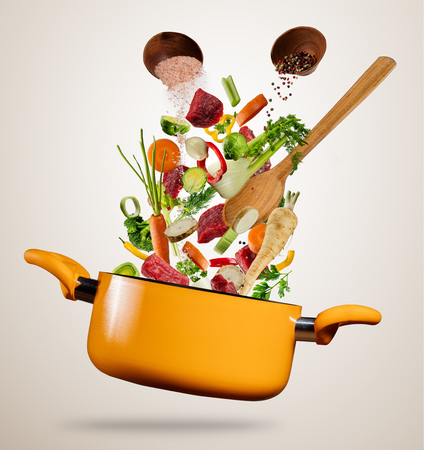 Fresh vegetable and pieces of beef meat flying into a pot with wooden spoon, separated on gray background