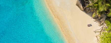 Aerial photo of beautiful sandy tropical beach with young woman sunbathing. Concept of summer travel vacation and relaxation Stock Photo