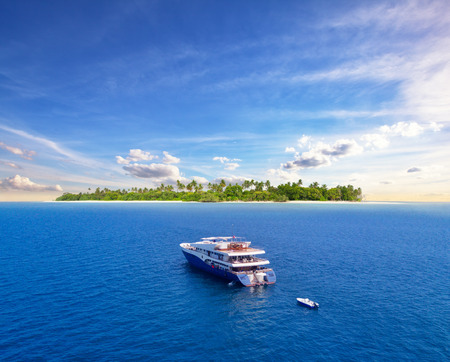 Big safari luxury yacht sailing on ocean in Maldives, tropical island on background. Concept of travel vacation and vessel trip Reklamní fotografie - 74585829