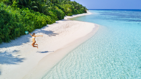Beautiful young woman jumping on tropical beach on Maldives. Concept of freedom ,vacation, travel and beach holidays. Summer theme. Stock Photo