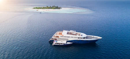 Big safari luxury yacht sailing on ocean in Maldives, tropical island on background. Concept of travel vacation and vessel trip Stock Photo