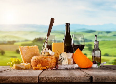 emmental: Various kind of cheese served on wooden table. Italian Toscana landscape on background. Traditional pieces of french and italy hand-made cheese. Copyspace for text