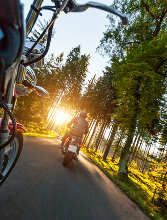moto: Two motorbikers riding on empty road in forest with sunrise light, concept of speed and travel in nature
