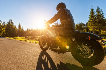 Dark motorbiker riding high power motorbike in nature with beautiful sunrise light