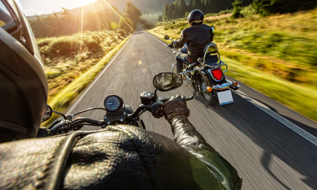 Two motorbikers riding on empty road with sunrise light, concept of speed and travel in nature