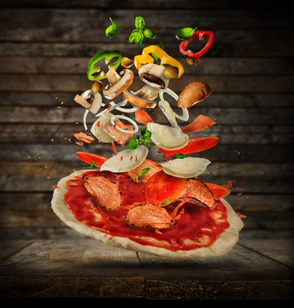 Concept of flying ingredients with pizza dough, placed on wooden planks background. Food preparation, fresh meal ready for cooking Stock Photo