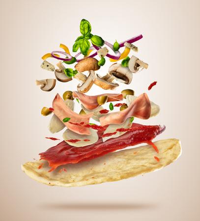 Concept vliegende ingrediënten met pizza deeg, geïsoleerd op lichte achtergrond. Voedselbereiding, verse maaltijd klaar voor koken