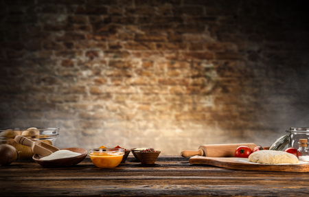 Baking ingredients placed on wooden table, ready for cooking. Copyspace for text. Concept of food preparation, dark background.