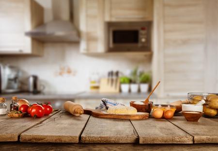 Baking ingrediënten geplaatst op houten tafel, klaar om te koken. Copyspace voor tekst. Concept van voedselbereiding, keuken op de achtergrond.