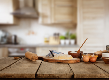 Baking ingredients placed on wooden table, ready for cooking. Copyspace for text. Concept of food preparation, kitchen on background.