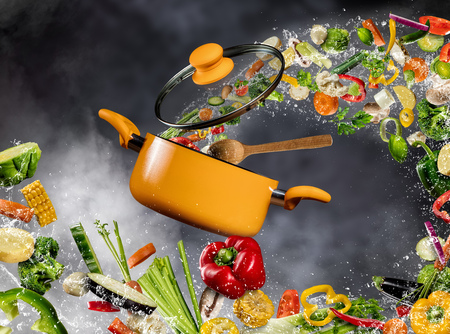 żywności: Świeże warzywa w wodzie powitalny latające w garnku z drewnianą łyżką, oddzielone na ciemnym tle. Pojęcie przygotowywania potraw i gotowania Zdjęcie Seryjne