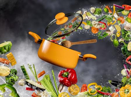 Verse groente in water splash vliegen in een pot met houten lepel, gescheiden op donkere achtergrond. Concept van voedselbereiding en koken