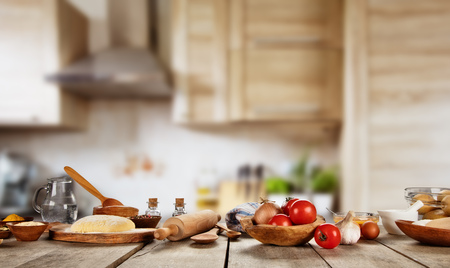 Baking ingredients placed on wooden table, ready for cooking pizza. Copyspace for text. Concept of food preparation, kitchen on background.