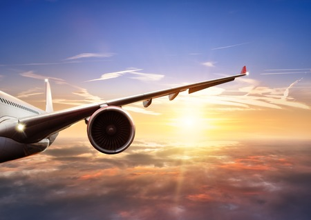 Detail of wing of commercial jet airplane flying above clouds in beautiful sunset light. Front view. Air travel and vacation concept. Banque d'images
