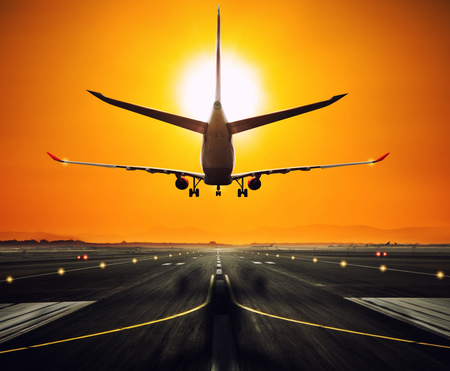 Silhouette from a landing airplane at the runway. Beautiful sunset sky. Travel and transportation concept Stock Photo