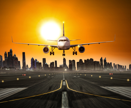 Landing commercial airplane at the runway, modern city with skyscrapers silhouettes on background