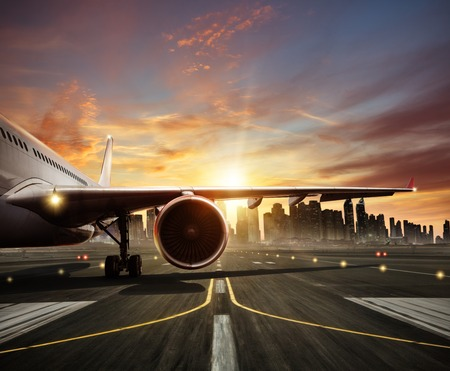 Detail of commercial airplane staying at the runway, wing and jet engne. Modern city with skyscrapers silhouettes on background Stockfoto