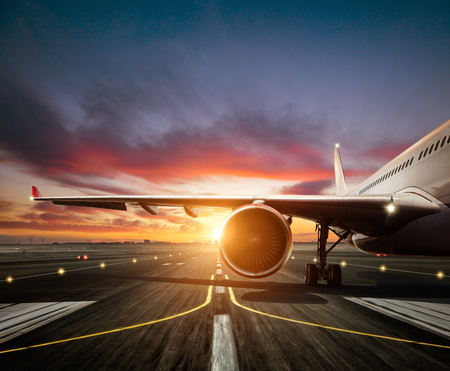 Detail of commercial airplane staying at the runway, wing and jet engne. Modern cityscape silhouettes on background