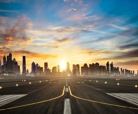 Luchthavenbaan met moderne wolkenkrabberssilhouetten op achtergrond in mooi zonsonderganglicht. Bewolkte hemel en zonnestralen. Reis- en stedenconcept