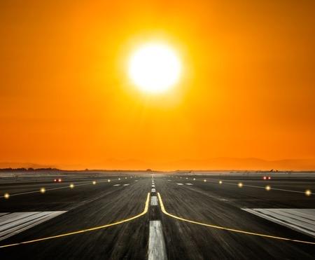 美しい夕日の光で背景に近代的な高層ビルのシルエットと空港の滑走路。曇り空と太陽光線。旅行や都市の概念