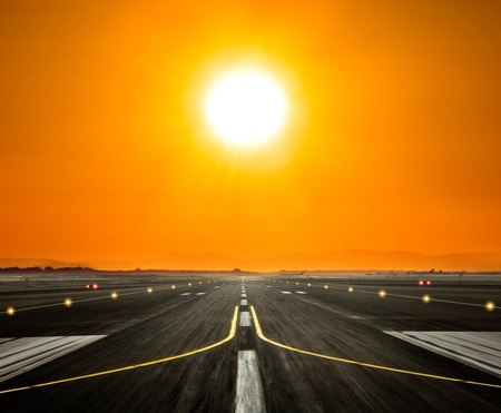 Airport runway with modern skyscrapers silhouettes on background in beautiful sunset light. Cloudy sky and sun rays. Travel and cities concept Stock Photo