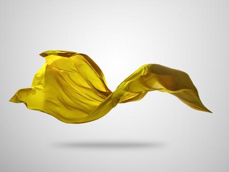 滑らかなエレガントなゴールド透明な布は、灰色の背景に分離。飛んでファブリックのテクスチャです。 写真素材