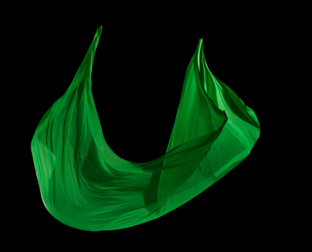 Smooth elegant green cloth separated on black background. Texture of flying fabric.