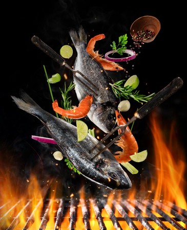 Flying raw whole bream fish and prawns, with ingredients for cooking above grill fire. Freeze motion of cooking staff. Fork holding the meat. Concept of food preparation in low gravity mode. Stock Photo