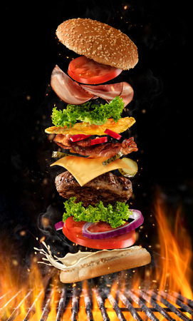 Flying burger ingredients above grill fire. Concept of low gravity motion and meal preparation. Isolated on black background