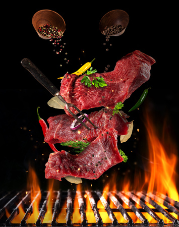 Flying pieces of raw steaks, with ingredients for cooking, barbecue grill with fire flames. Concept of food preparation in low gravity mode. Separated on smooth background