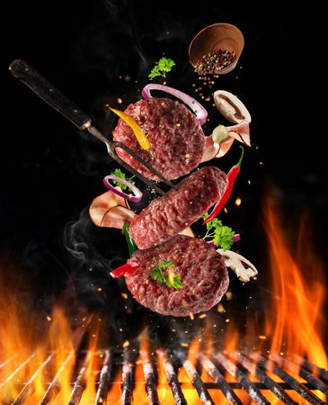 Flying raw milled beef meat, with ingredients for cooking above grill fire. Freeze motion of cooking staff. Fork holding the meat. Concept of food preparation in low gravity mode.