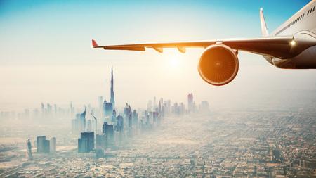Close-up van commercieel vliegtuig dat over moderne stad vliegt. Concept van snel vervoer en reizen.