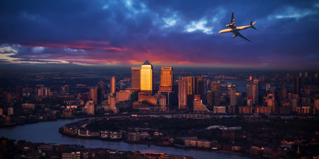 Passengers airplane flying above modern London city in the sunset light. Transportation and travel, European destination, skyscrapers