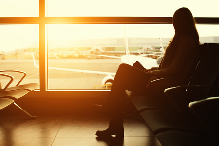 Silhouette of a young woman traveler waiting at the airport for thedeparture. Travel and business concept