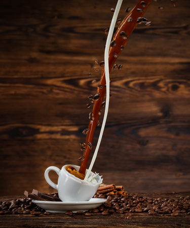 Splashing liquid of coffee and milk into white cup placed on wooden table. Coffee beans falling around