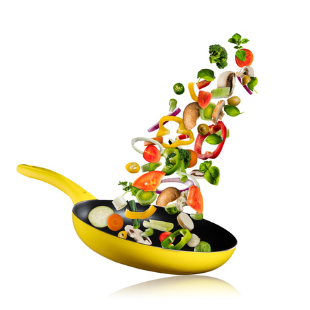 Fresh vegetables flying into a pan, isolated on white background. Concept of flying food, preparation, diet and healthy eating. Stockfoto