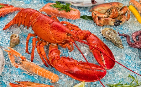Whole lobster with seafood, crab, prawns, oyster and other shells served on crushed ice.