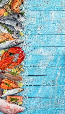 Whole lobster with seafood, crab, mussels, prawns, fish, salmon steak, mackerel and other shells served on crushed ice and wooden table