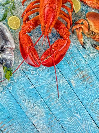 Hele kreeft met zeevruchten, krab, mosselen, garnalen, vis, zalmlapje vlees geserveerd op gemalen ijs en houten tafel