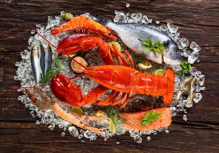 신선한 해산물, 바다 가재, 게, 홍합, 새우, 생선, 게, 연어 스테이크, 도미 생선 및 기타 조개류가 오래된 나무 테이블에 제공됩니다. 스톡 콘텐츠