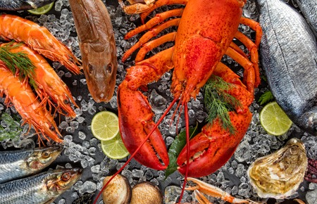 Whole lobster with seafood, mussels, prawns, fish, salmon steak, octopus, oyster and other shells served on crushed ice. Stock Photo