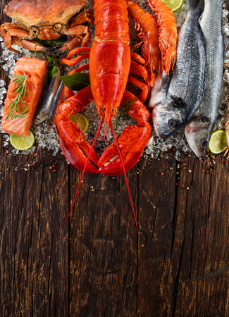 Whole lobster with seafood, crab, mussels, prawns, fish, and other shells served on crushed ice and wooden table Stock Photo