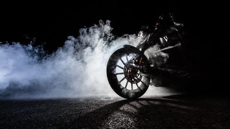 夜人ライダーとハイパワー バイク チョッパーのディテール。霧の背景にバックライト付き。
