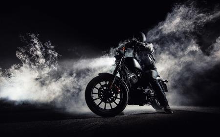 rejas de hierro: Chopper de la motocicleta del poder más elevado con el jinete del hombre en la noche. Niebla con retroiluminación en el fondo.