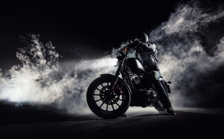 High power motorcycle chopper with man rider at night. Fog with backlights on background. Foto de archivo