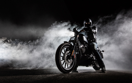 High power motorcycle chopper with man rider at night. Fog with backlights on background. 免版税图像
