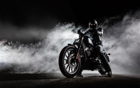 Hoge motor motorhacker met man rider 's nachts. Mist met backlights op de achtergrond.