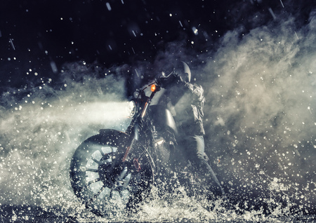 Detail of high power motorcycle chopper with man rider at night. Fog with backlights on background. Water splash on foreground Stock Photo
